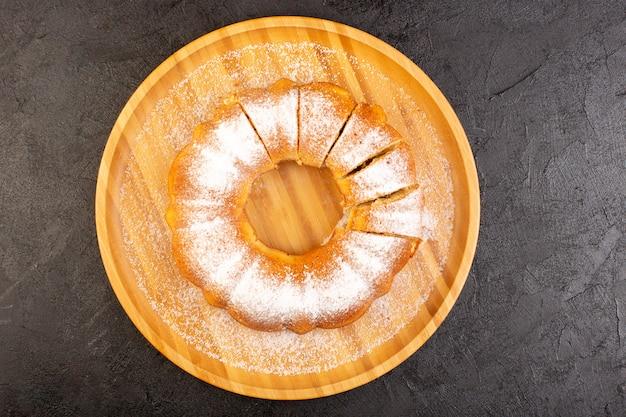 Вид сверху нарезанный порошкообразный торт сладкий вкусный запеченный круглый на деревянном столе сладкое печенье кондитерское Бесплатные Фотографии