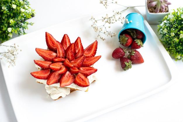 Вид сверху нарезанной красной клубники с сочными сочными ягодами внутри белого стола вместе с цельной клубникой и растениями по всему фруктовому десерту на белом полу. Бесплатные Фотографии