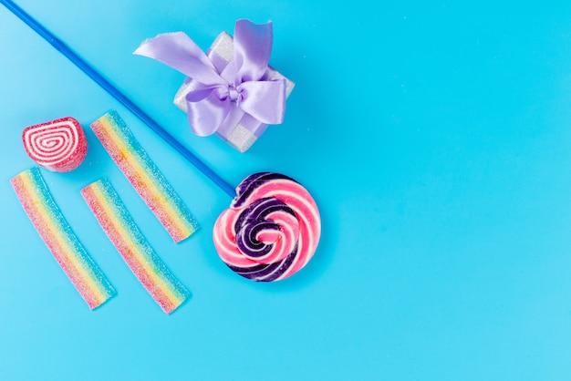 青い棒と青い机の上の小さな紫のギフトボックス、甘い砂糖の誕生日のトップビュー甘いロリポップ 無料写真