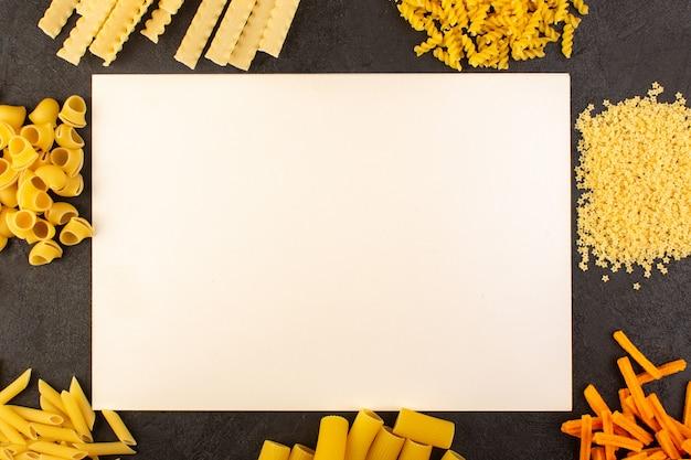 暗い背景の食事食品イタリアパスタに分離された別の形成された黄色の生パスタと共に木製のトップビューホワイトデスク 無料写真