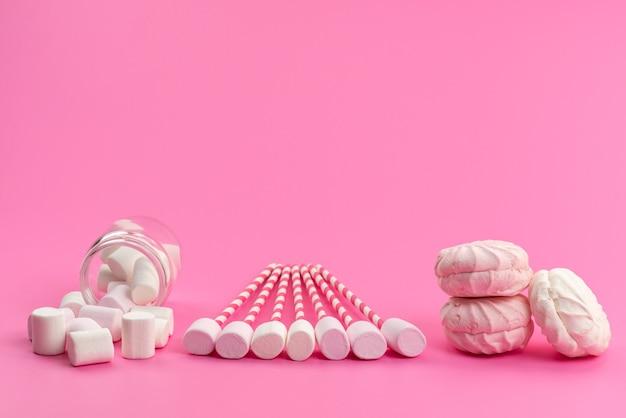 ピンクの机の上のメレンゲと一緒にピンクの棒の上面の白いマシュマロ、砂糖の甘い色 無料写真