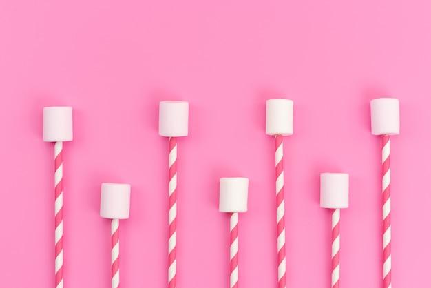ピンクの机の上にピンクの棒が付いた平面図の白いマシュマロ、砂糖の甘い色 無料写真