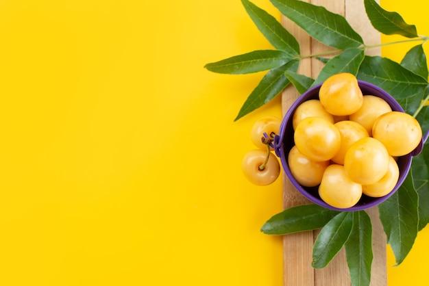トップビュー黄色いサクランボのまろやかで甘い、黄色の机の上の緑の葉、果実色の夏の甘いチェリー 無料写真