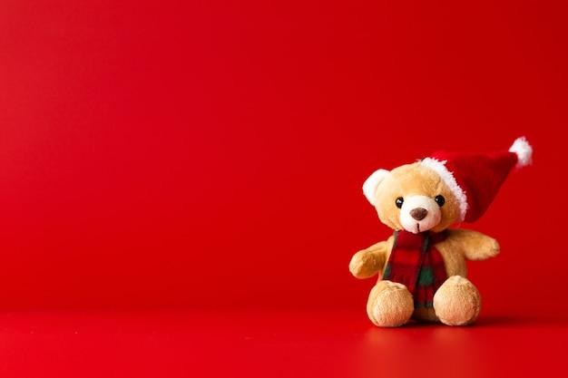 На красном фоне сидит игрушечный медведь в красной шапке и шарфе. горизонтальное фото Premium Фотографии