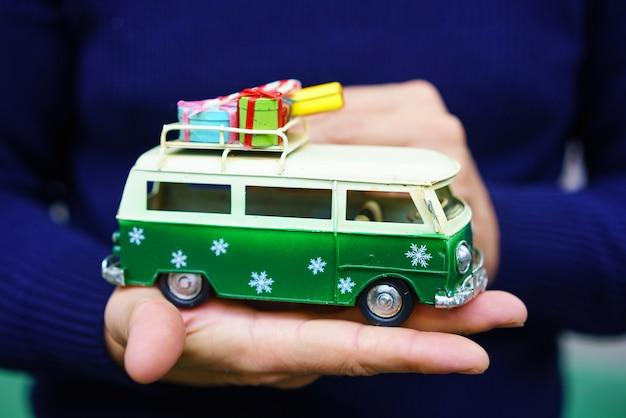 Игрушечный зеленый праздничный автобус с подарками на крыше стоит на руке. елочный декор Бесплатные Фотографии