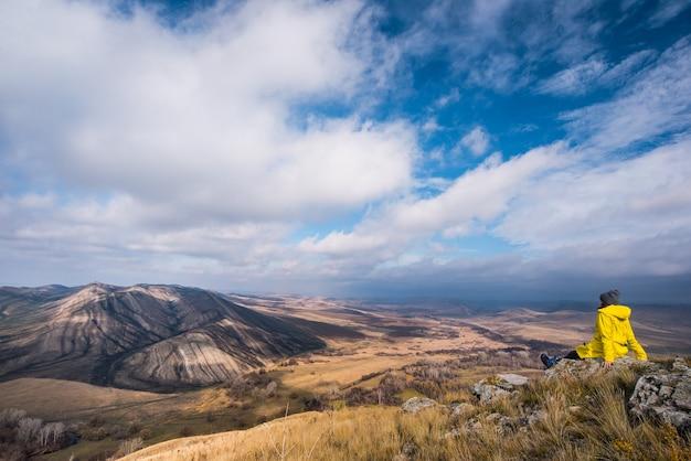 Путешественник сидит на холме и небольшой горе осенью и смотрит вдаль Premium Фотографии