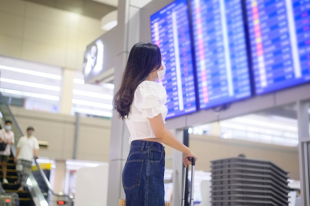 旅行者の女性は国際空港で防護マスクを着用し、covid-19パンデミック下で旅行、安全旅行、社会的距離のプロトコル Premium写真