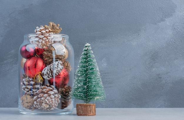 나무 입상과 대리석 표면에 크리스마스 장식품으로 가득한 타락한 항아리 무료 사진