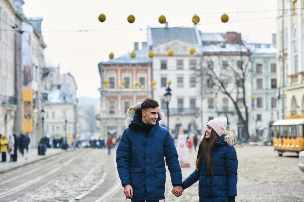Модная молодая пара гуляет по городу в зимний сезон. Premium Фотографии