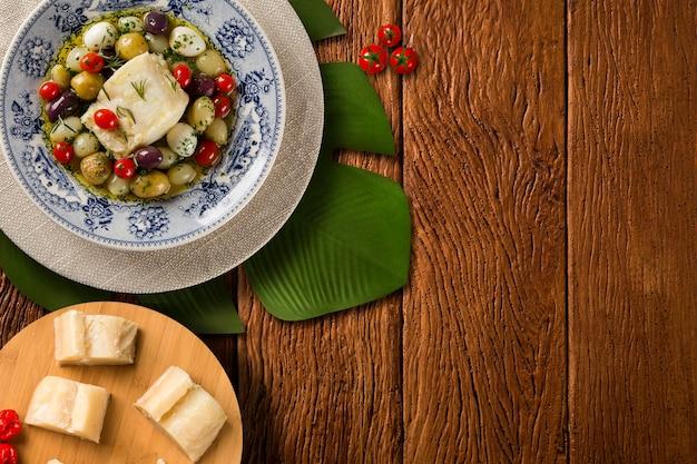 Типичное португальское блюдо с треской под названием bacalhau do porto в оригинальной португальской тарелке. Premium Фотографии