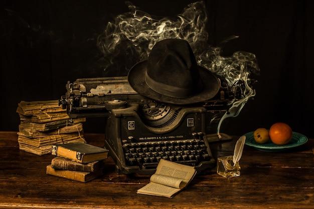 Печатная машина, шляпа-федора и старые книги на деревянном столе Бесплатные Фотографии