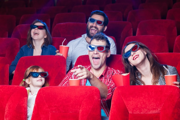 Разнообразие человеческих эмоций от друзей, держащих колу и попкорн в кинотеатре. Бесплатные Фотографии
