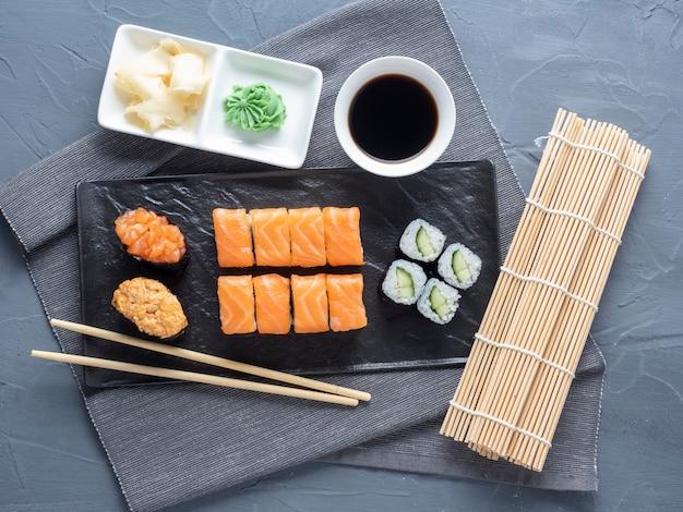 黒いプレートに入れ子になった様々な巻き寿司と寿司軍艦。その隣には竹わさびのスティックとソースがあります。上面図、フラットレイ。伝統的な日本料理 Premium写真