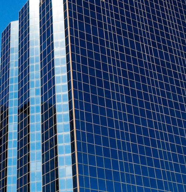 Вертикальный снимок высокой башни с синими окнами Бесплатные Фотографии
