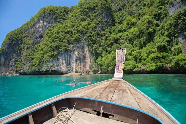 観光客がシュノーケリングや海、ピピ島、タイでダイビングしながらタイの伝統的なロングテールボートからの眺め Premium写真