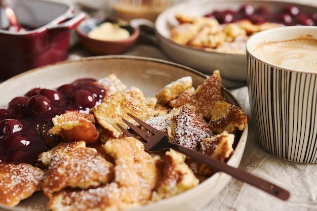 さくらんぼと粉砂糖が入ったふわふわのおいしいパンケーキの眺め 無料写真