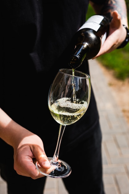 Официант наливает белое вино в бокал Premium Фотографии