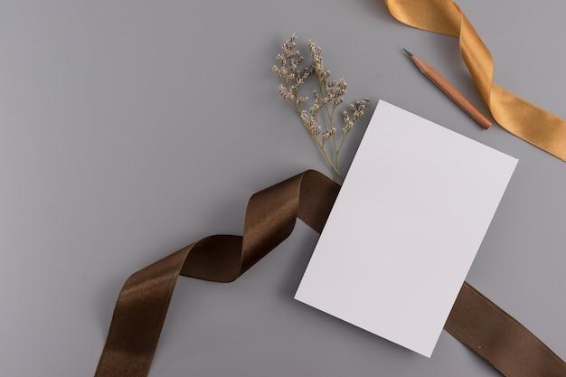 結婚式のコンセプト。結婚式招待状リボンと装飾の灰色の背景にカード。 Premium写真