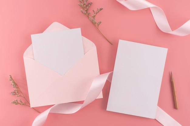 結婚式のコンセプト。結婚式の招待状、ピンクの背景にリボンと装飾が付いています。 Premium写真