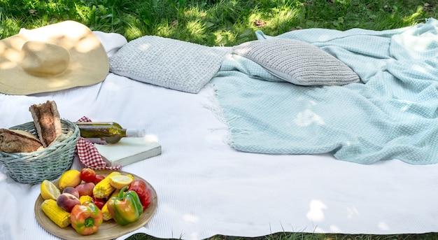 緑の草の上の白い毛布。ピクニックのコンセプト。 無料写真