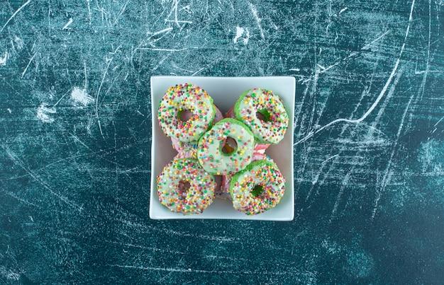 파란색 배경에 달콤한 도넛의 전체 흰색 그릇. 고품질 사진 무료 사진