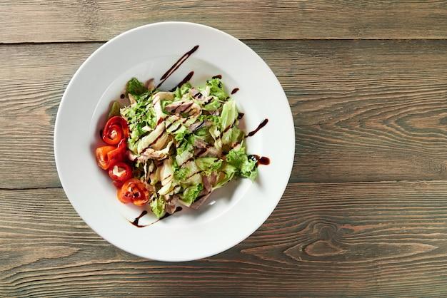 グリルしたチキン、パプリカ、レタスの葉とソースの野菜サラダがいっぱい入った白いボウル。デリシオスで美味しそう。 無料写真