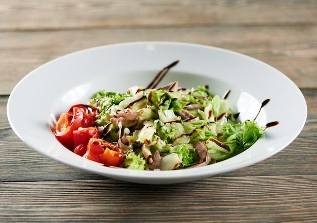 木製のテーブルに白いボウル。チキン、パプリカ、レタスの葉の軽い野菜サラダが付いています。美味しくて美味しそう。 無料写真