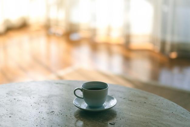 Белая кружка горячего кофе на столе у занавески в доме Premium Фотографии