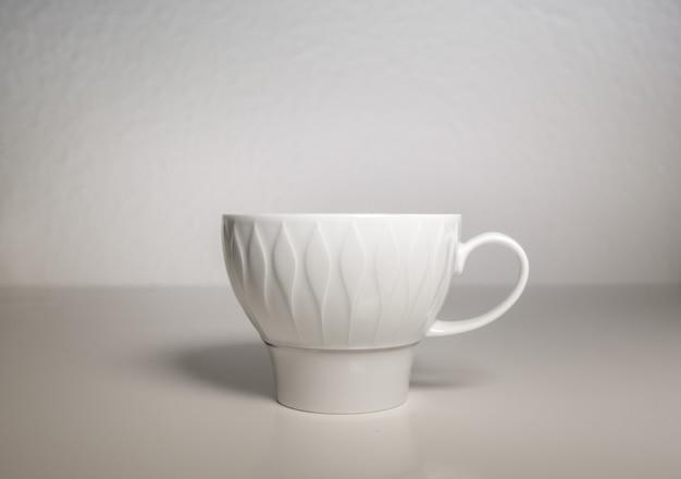 白い背景の上の白い磁器のカップ 無料写真