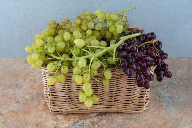 大理石のテーブルに甘いブドウがいっぱい入った籐のバスケット。 無料写真