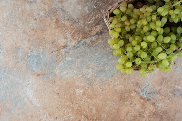 Плетеная корзина, полная сладкого винограда на мраморном столе. Бесплатные Фотографии