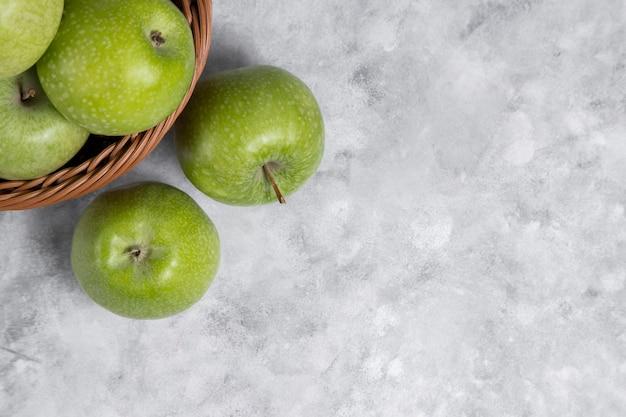 石の上の新鮮な青リンゴの籐のバスケット 無料写真