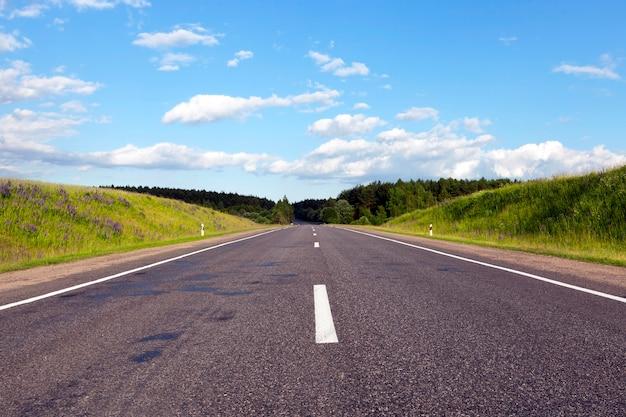 さまざまな木々が生い茂る森、青空の晴天の中を通るアスファルトの広い道 Premium写真