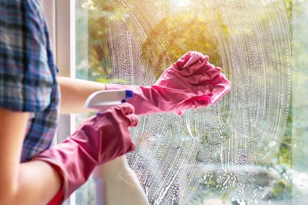 Женщина протирает оконное стекло тряпкой и мыльной пеной. чистка моющим средством. руки в розовых защитных перчатках, моющих стекло на окнах дома с распылителем, домашняя рутинная концепция. Premium Фотографии