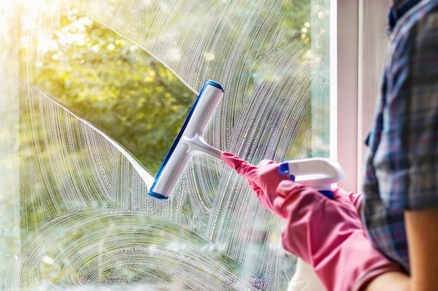 Женщина чистит оконное стекло ракелем и мыльной пеной. чистка моющим средством. руки в розовых защитных перчатках, моющих стекло на окнах с распылителем, домашний распорядок, концепция работы по дому. Premium Фотографии