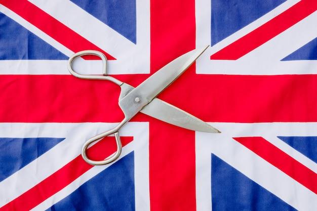 抗議で女性がハサミで英国国旗を切る。 Premium写真