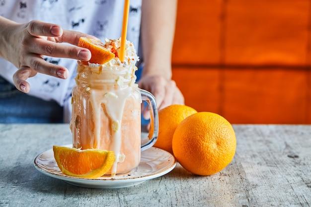 오렌지 스무디와 오렌지와 흰색 접시 한 조각을 들고 여자 손 무료 사진