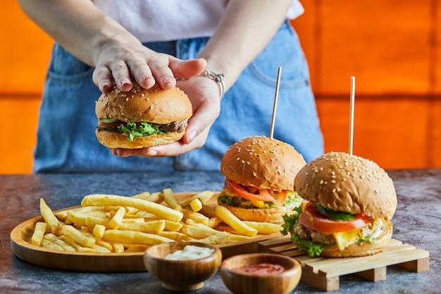 튀김 감자, 케첩, 마요네즈와 치즈 버거를 들고 여자 손 무료 사진
