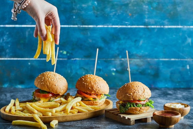 나무 접시에 세 치즈 버거, 케첩, 마요네즈와 감자 튀김을 들고 여자 손 무료 사진