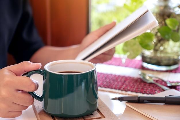 コーヒーを飲みながらノートを保持している女性 Premium写真