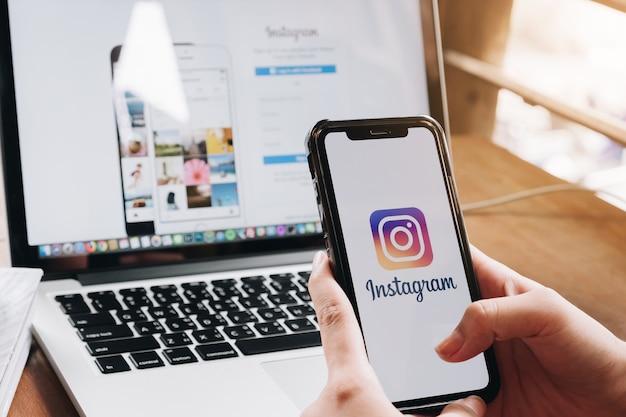 Женщина держит смартфон с приложением instagram на экране в кафе. Premium Фотографии