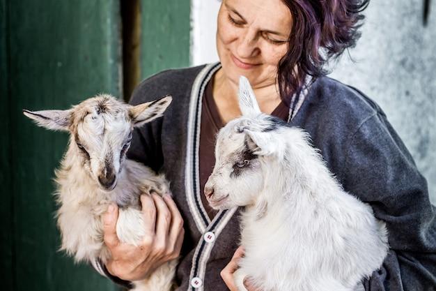 Женщина держит на руках маленьких маленьких козочек. любовь к питомцам. работа людей в сельском хозяйстве на ферме Premium Фотографии