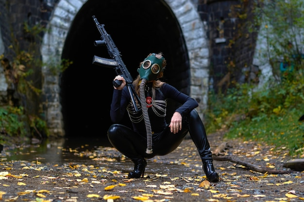 Женщина в черном костюме и противогазе с автоматом в руках. Premium Фотографии