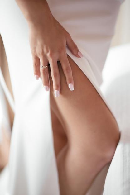 ドレスを着た女性が両手を足に沿って走らせる Premium写真