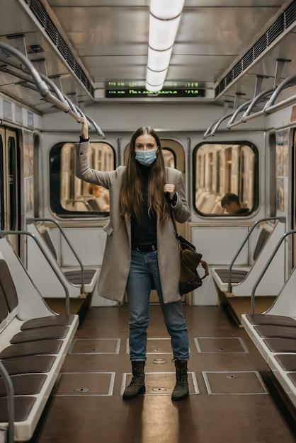 Женщина в медицинской маске во избежание распространения коронавируса держится за поручень в вагоне метро. девушка с длинными волосами в хирургической маске от covid-19 стоит в поезде метро. Premium Фотографии