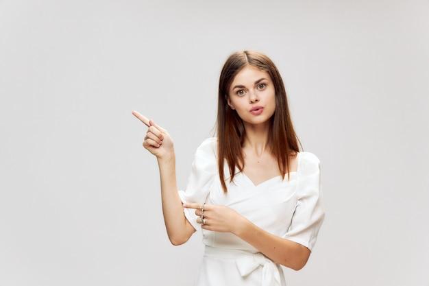 Женщина в белом платье показывает пальцами сбоку обрезанный вид на светлом фоне Premium Фотографии