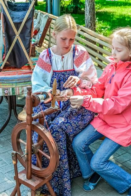 Женщина в национальной одежде учит девушку работать на ручной прялке Premium Фотографии