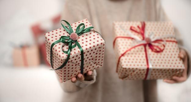 여자는 아름다운 크리스마스 선물을 들고있다. 무료 사진