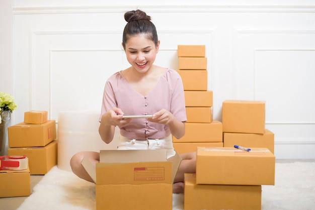 Женщина готовит продукты с картонными коробками к отправке. Premium Фотографии