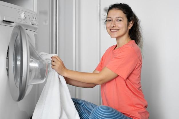 女性がアパートの床に座っている間に汚れた洗濯物を洗濯機に入れます。 Premium写真